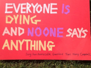 A placard reading 'Everyone is Dying and No-one Says Anything'